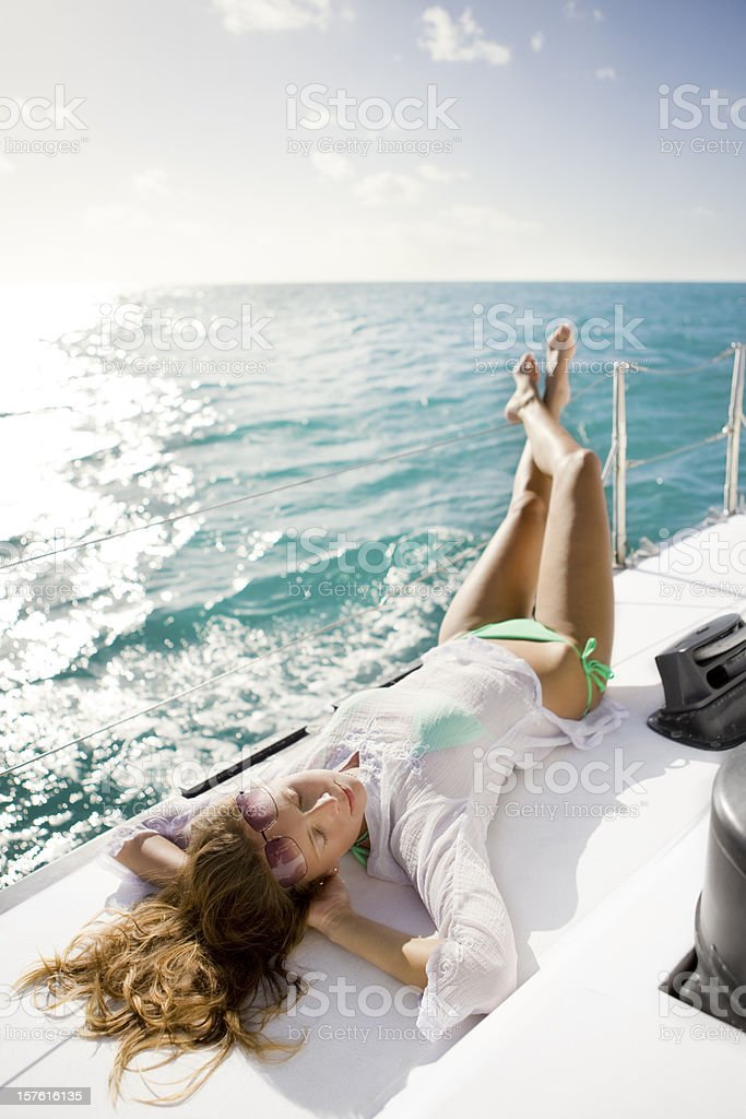 woman sunbathing on a sailboat sailing through the Caribbean stock photo
