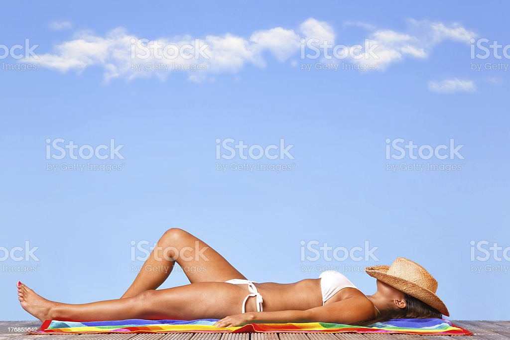 Woman sunbathing on a wooden deck stock photo