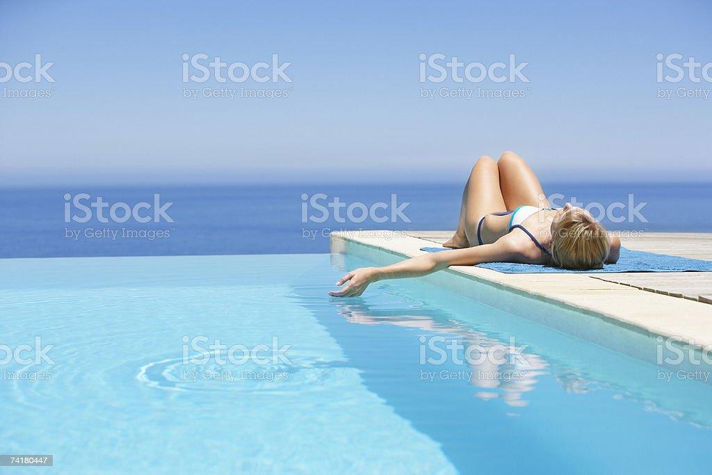 Woman sunbathing on deck with infinity pool stock photo