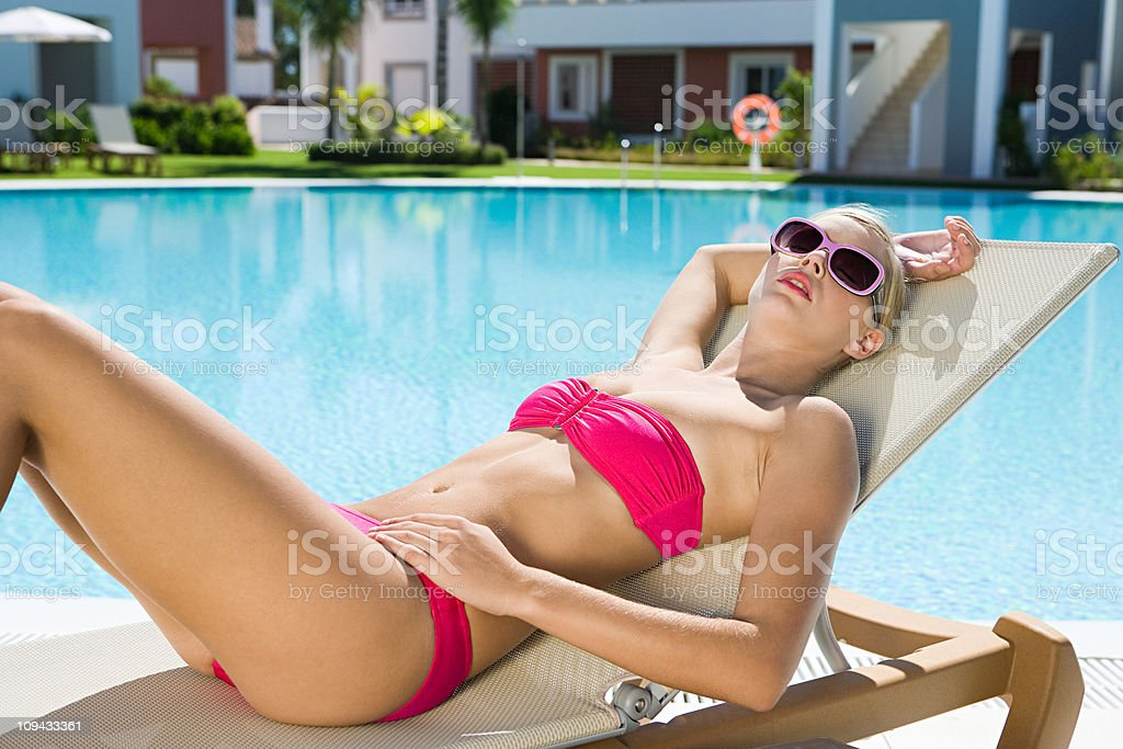 Woman sunbathing on sunlounger at poolside stock photo