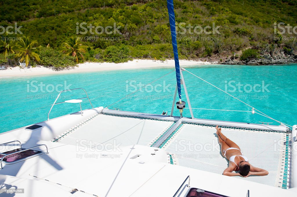 woman sunbathing on the sailboat anchored by Jost van Dyke stock photo