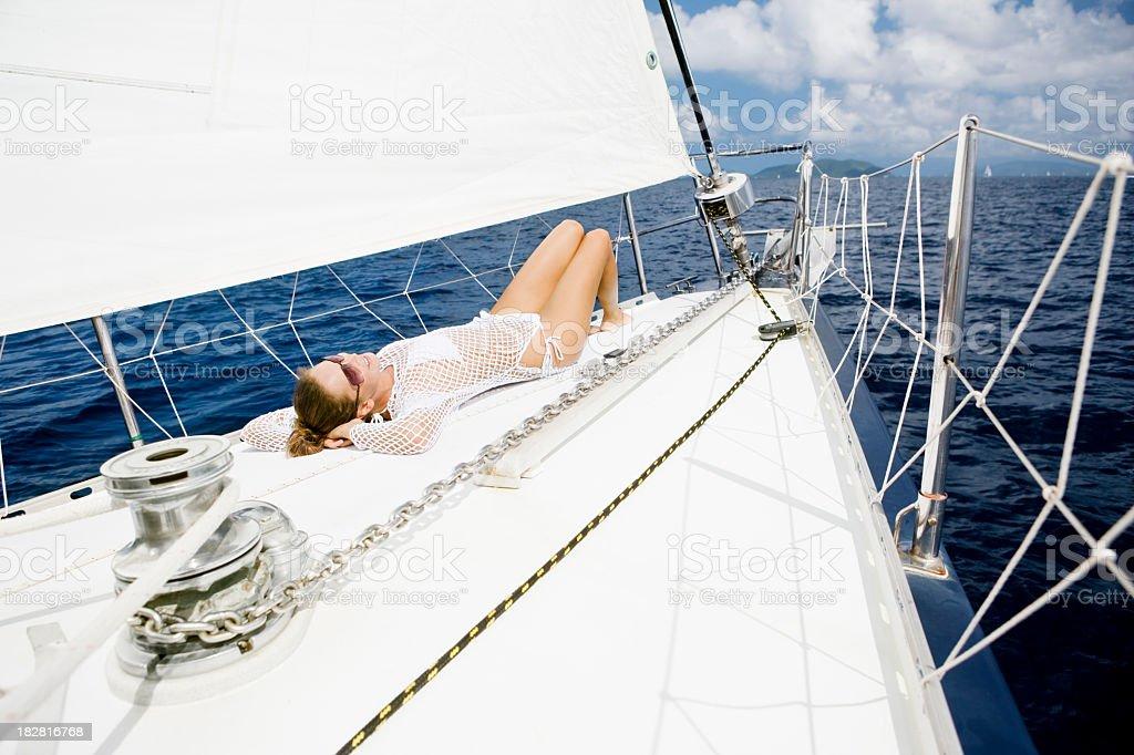 woman sunbathing on the sailboat royalty-free stock photo