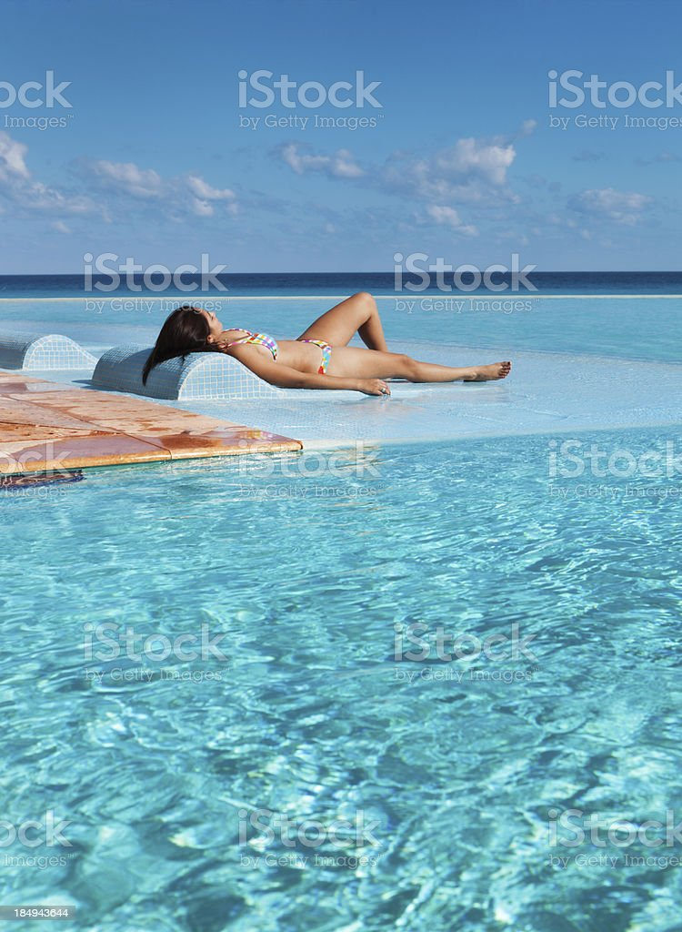 Woman Sunbathing on Vacation in Infinity Pool of Resort Hotel royalty-free stock photo