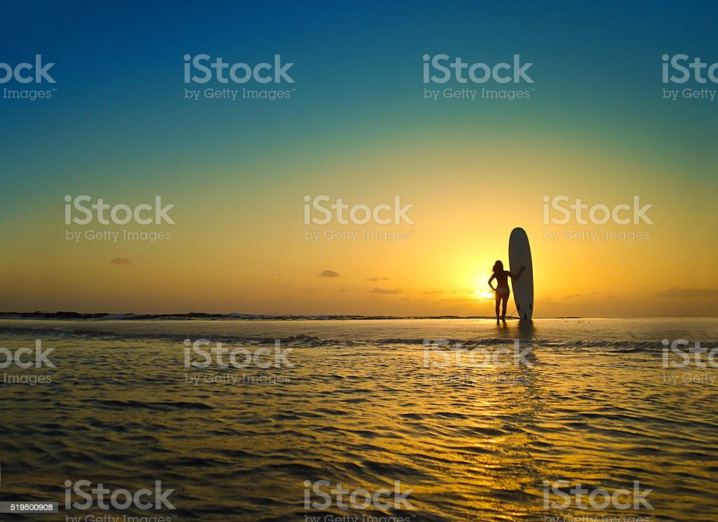 Woman Surfer on Beach at Sunset in Kauai Hawaii stock photo