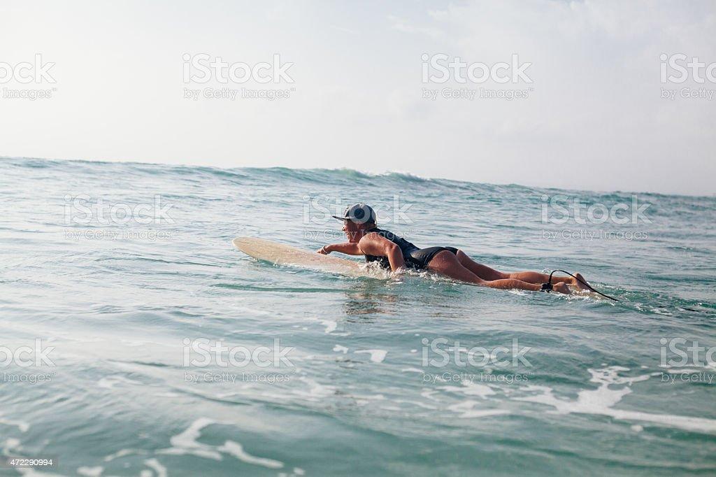 woman surfer swimming in sea stock photo