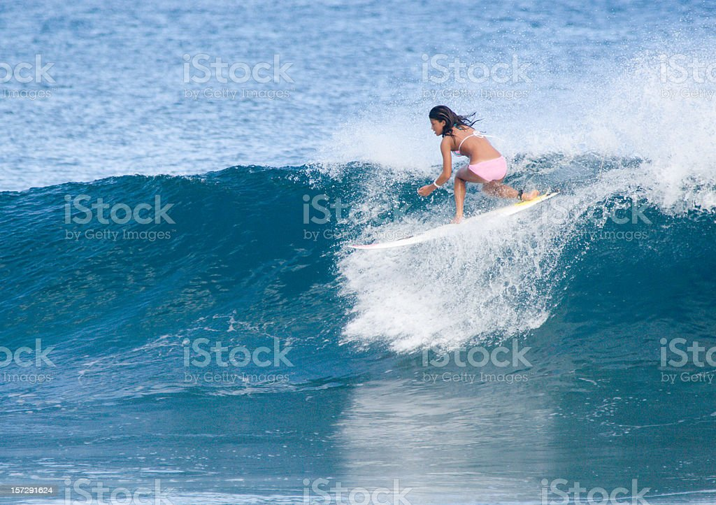 Woman surfing a wave by herself stock photo