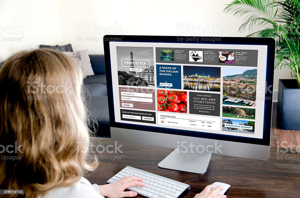 Woman surfing the internet from a desktop computer at home stock photo