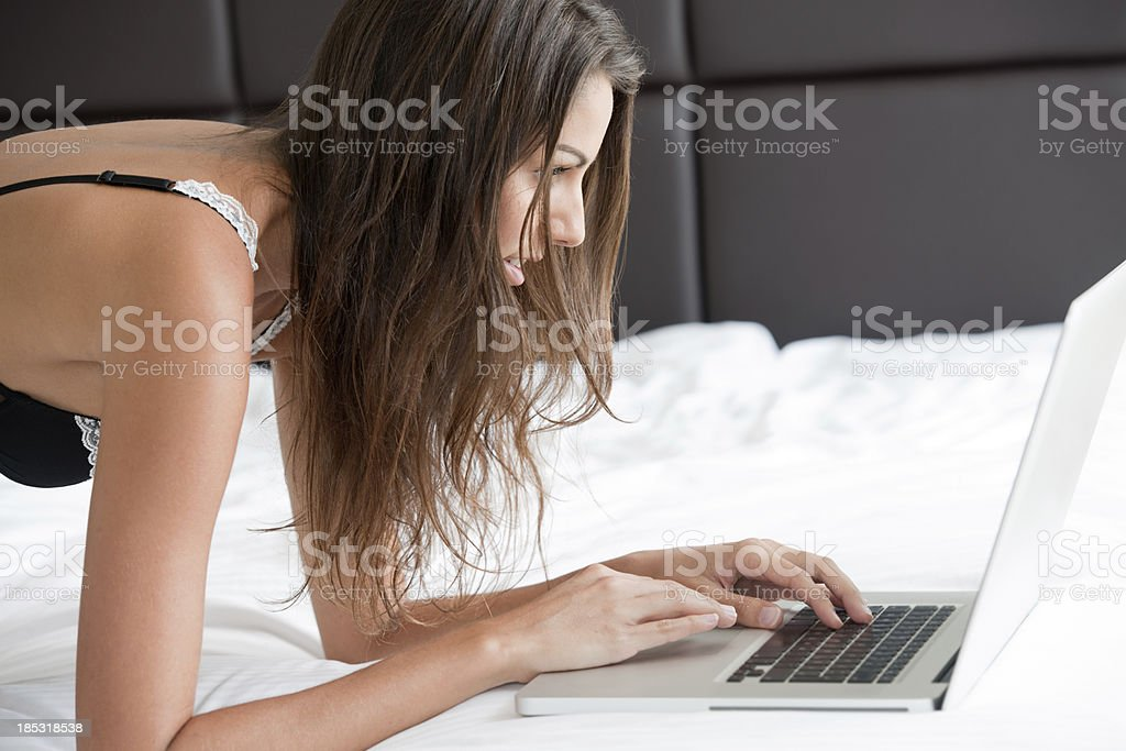 Woman surfing the web in Bed (XXXL) royalty-free stock photo