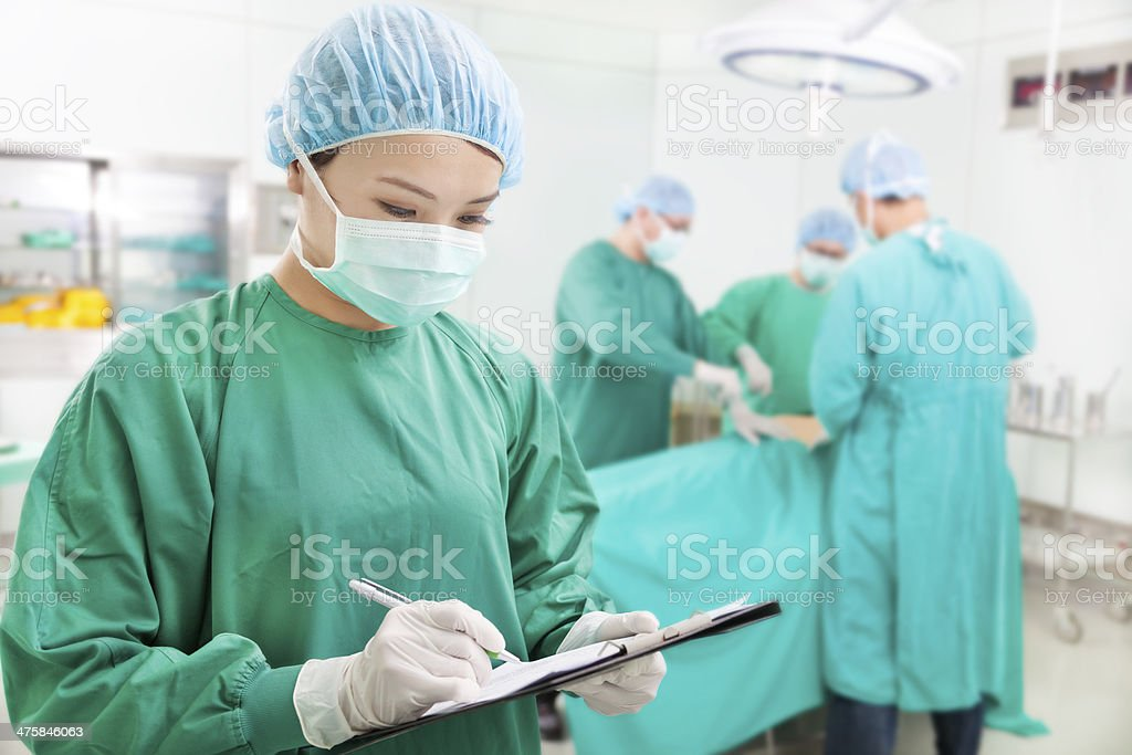 woman Surgeons writing records on form stock photo