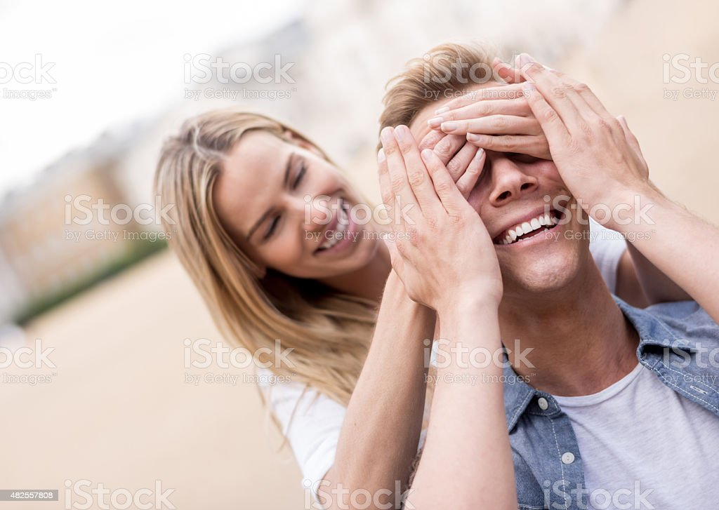 Woman surprising her boyfriend outdoors stock photo