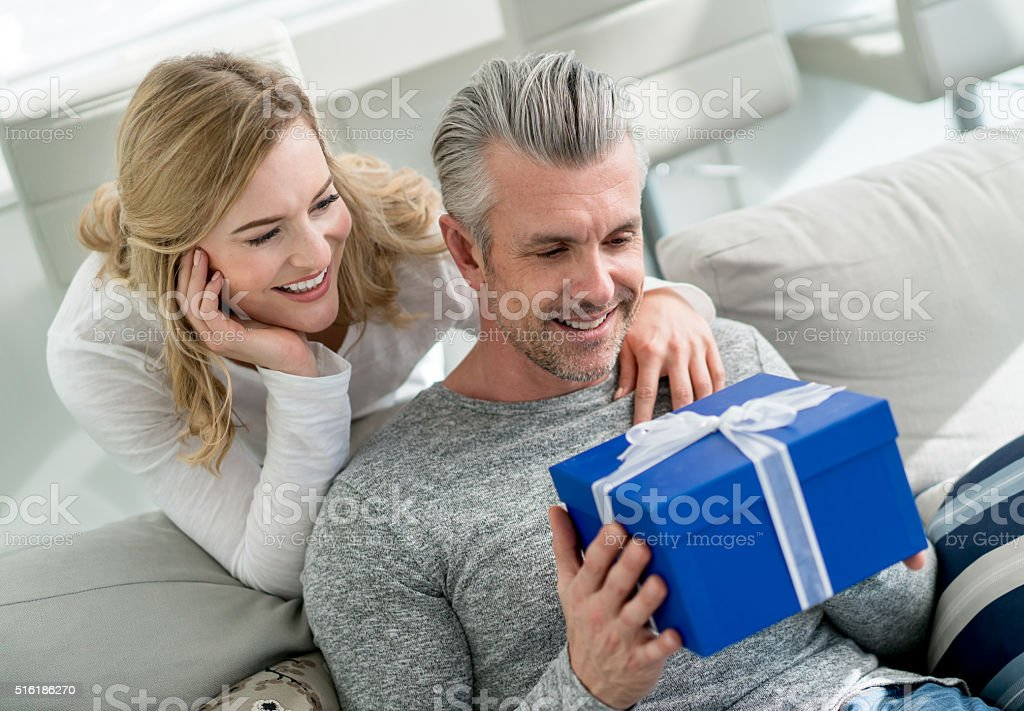 Woman surprising man with a present stock photo