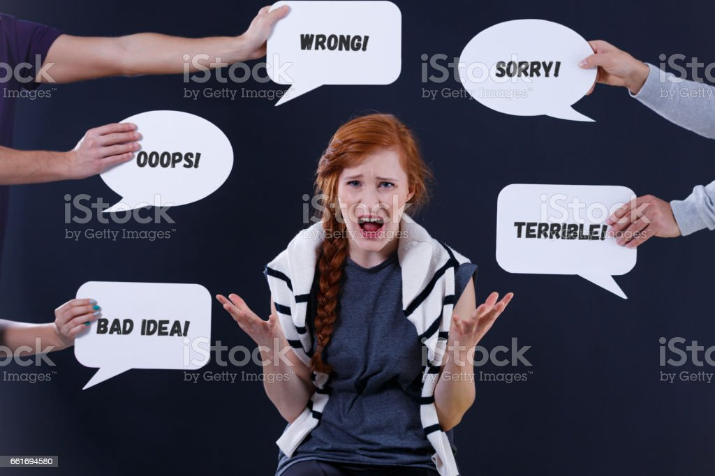 Woman surrounded by comments in speech bubbles stock photo
