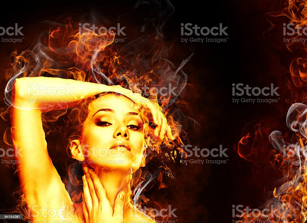 A woman surrounded by flames and white smoke stock photo