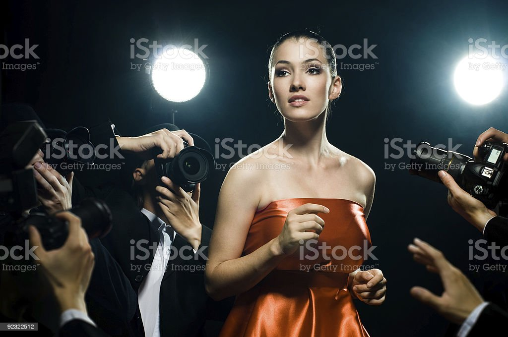 A woman surrounded by paparazzi stock photo