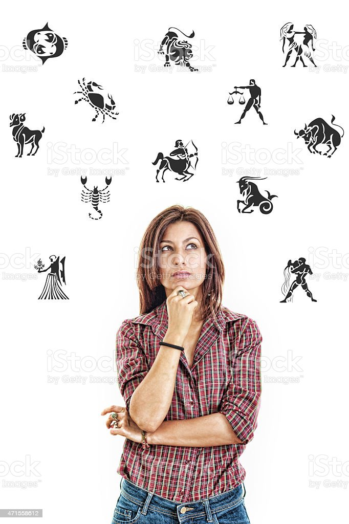 woman surrounded with zodiac signs thoughtfully looking up with stock photo