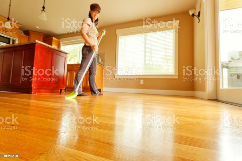 Woman Sweeping Hardwood Floor with Broom stock photo