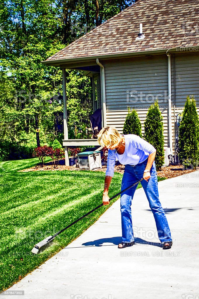 Woman sweeping her driveway with a broom stock photo