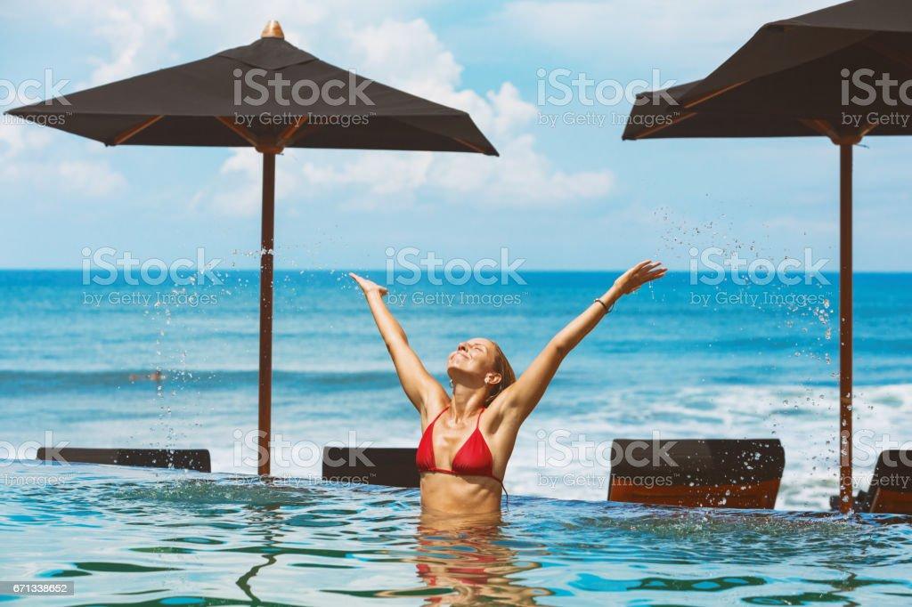 Woman swim in ocean beach infinity pool stock photo