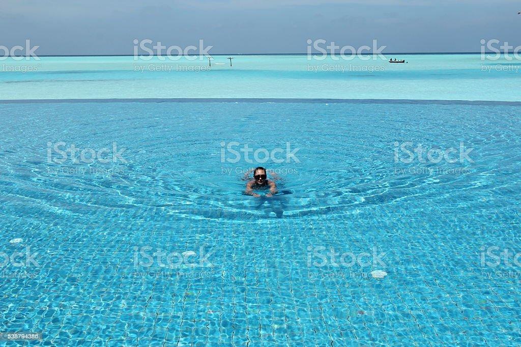 woman swimming  in infinity pool in Anantara Resort, Maldives stock photo