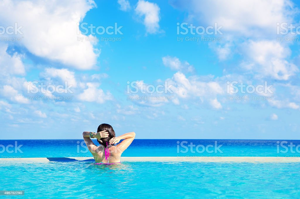 Woman Swimming in Infinity Pool of Hotel in Cancun Mexico stock photo