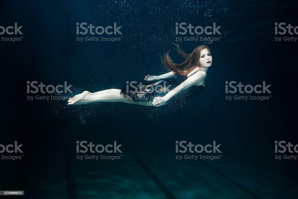 Woman swims underwater. stock photo