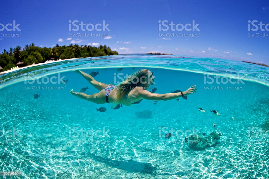 Woman swims with tropical fish in a lagoon stock photo