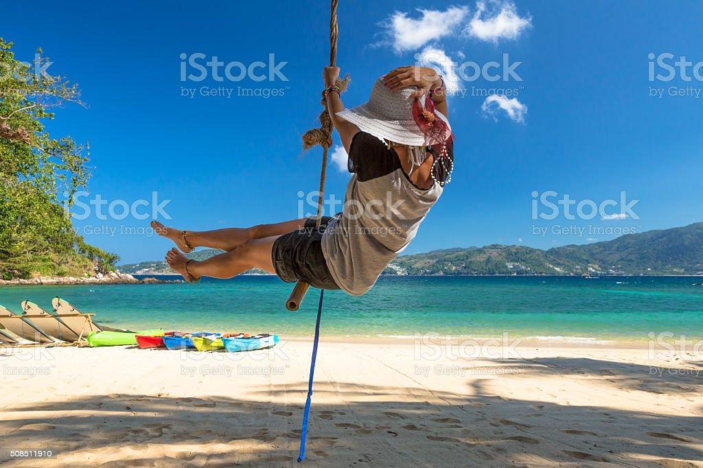 Woman swinging on the beach stock photo
