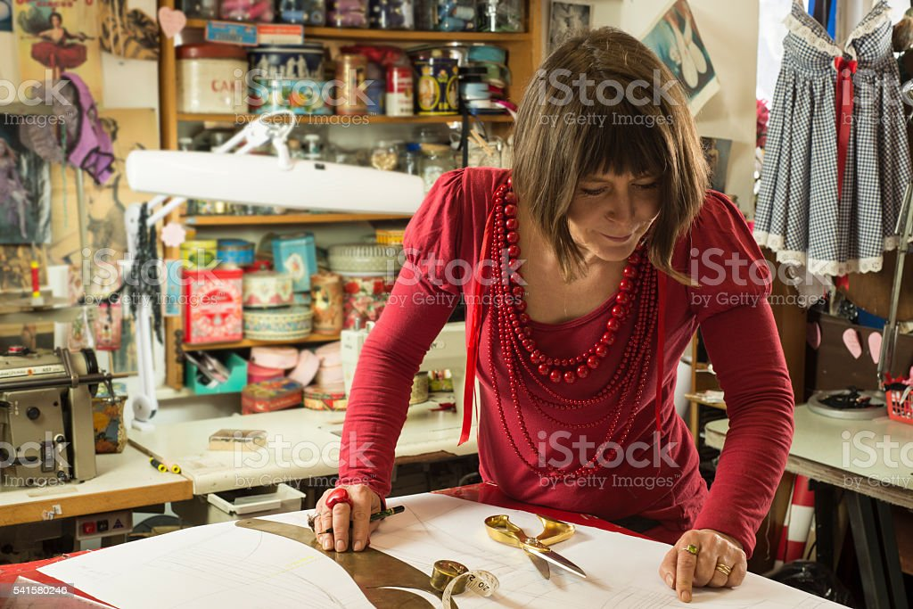 Woman Tailor in Red Measuring White CLoth stock photo