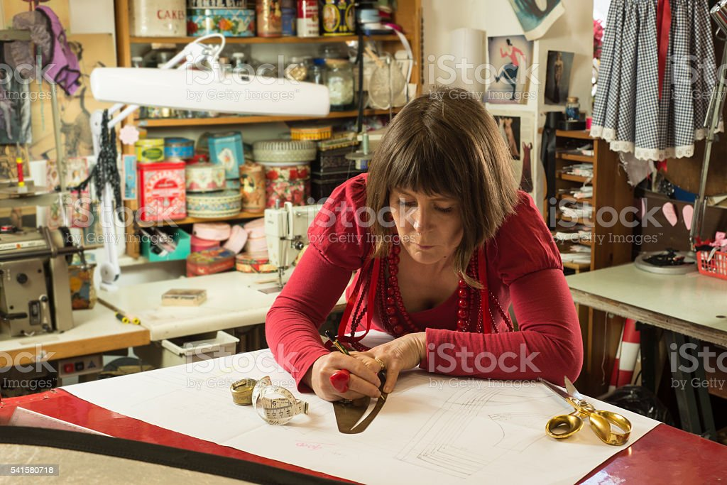 Woman Tailor in Red Tracing and Measuring White Paper stock photo