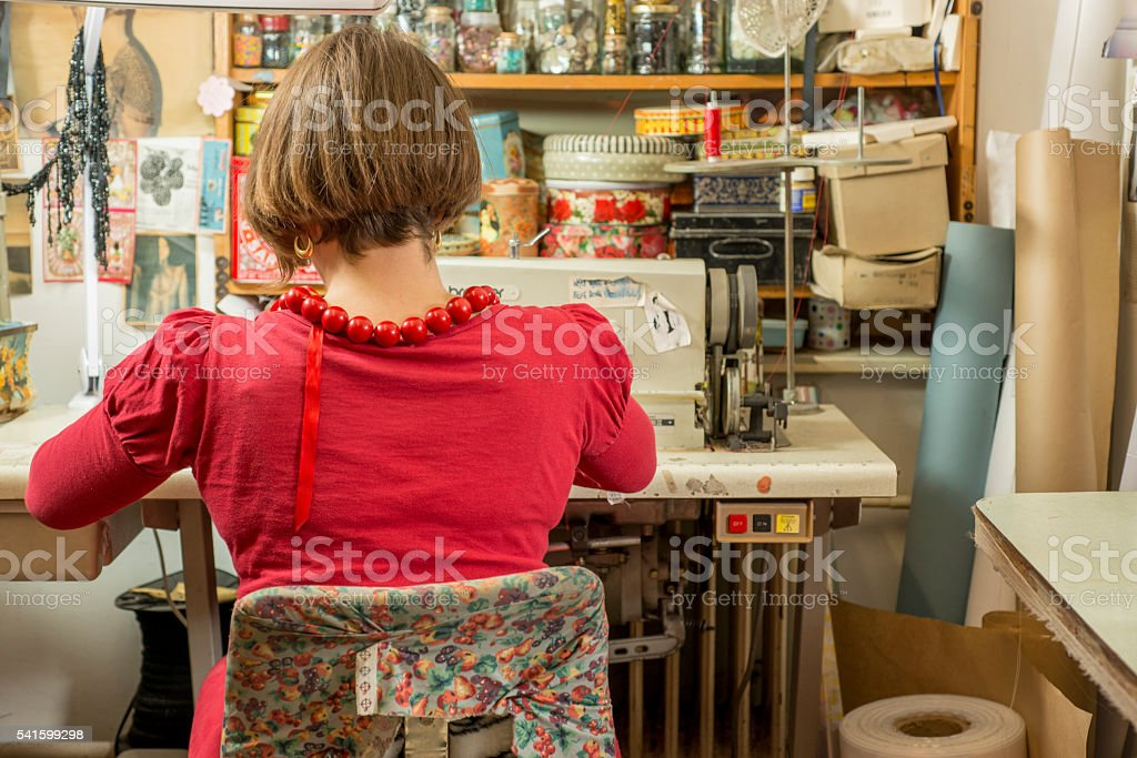 Woman Tailor Seated and Working on Sewing Machine stock photo