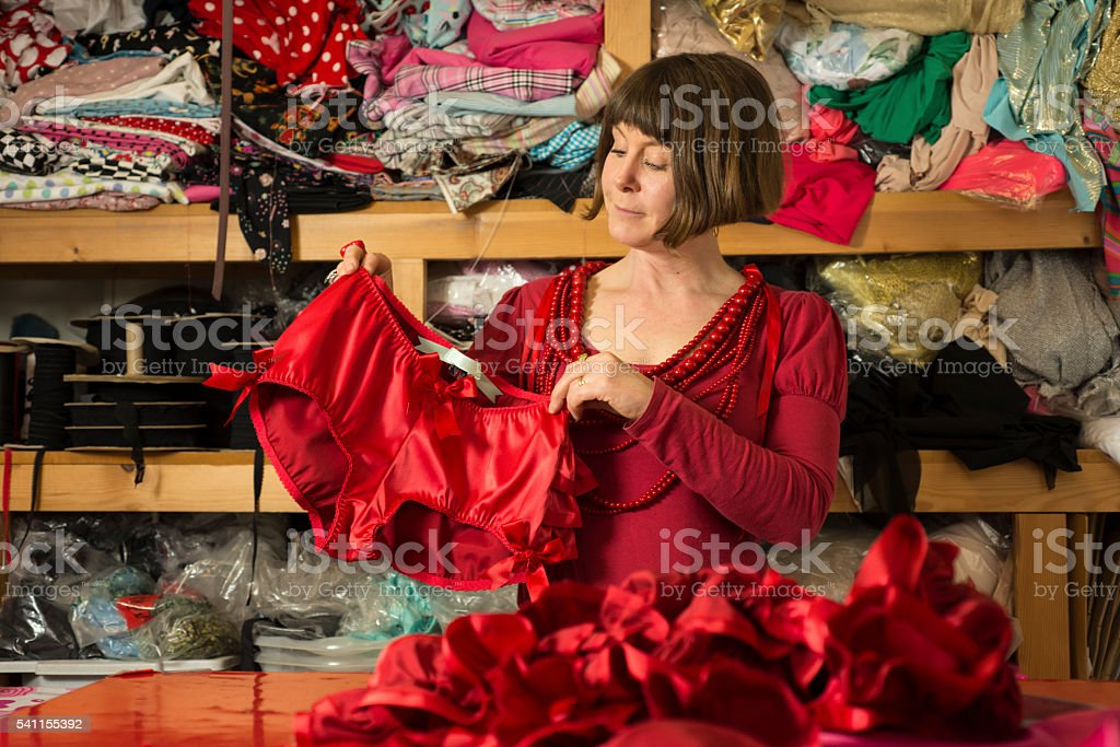 Woman Tailor Showing Off Newly Sewn Lingerie stock photo