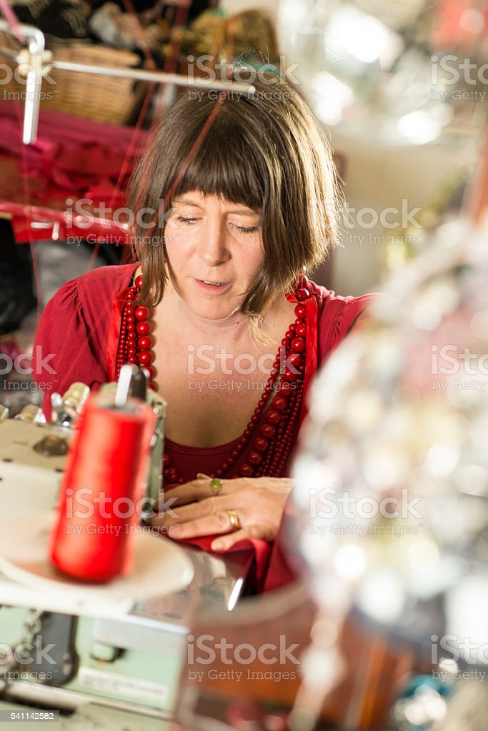 Woman Tailor Stitching Cloth Through a Sewing Machine stock photo