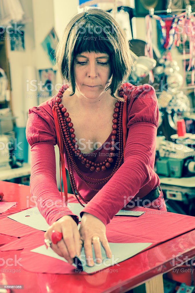 Woman Tailor Tracing Red Cloth stock photo