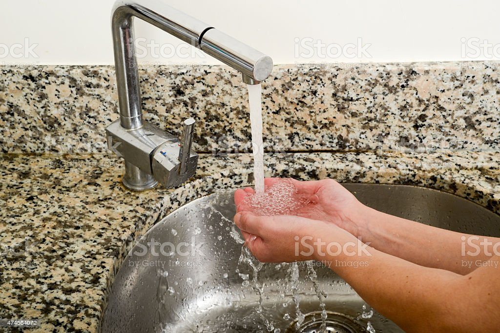 Woman takeing water with her hands from a tap stock photo