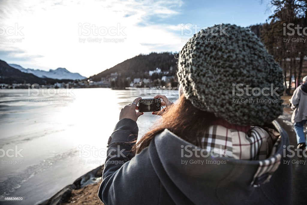 Woman takes a picture of a frozen lake stock photo