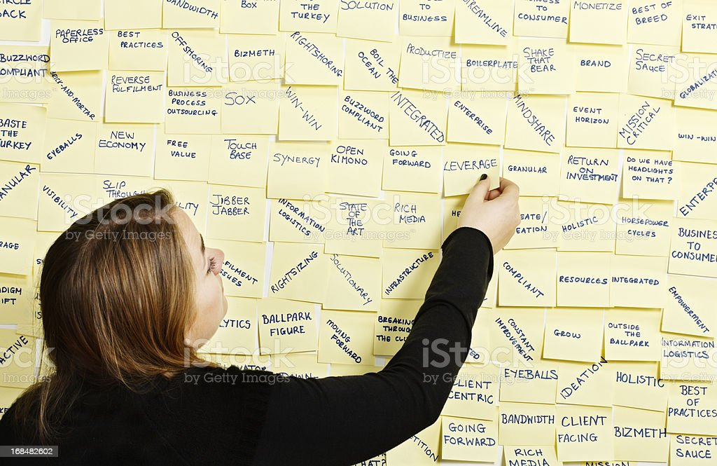 Woman takes note 'Leverage' from packed business buzzword noticeboard royalty-free stock photo