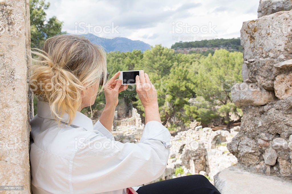 Woman takes smart phone pic of ancient Greek ruin stock photo