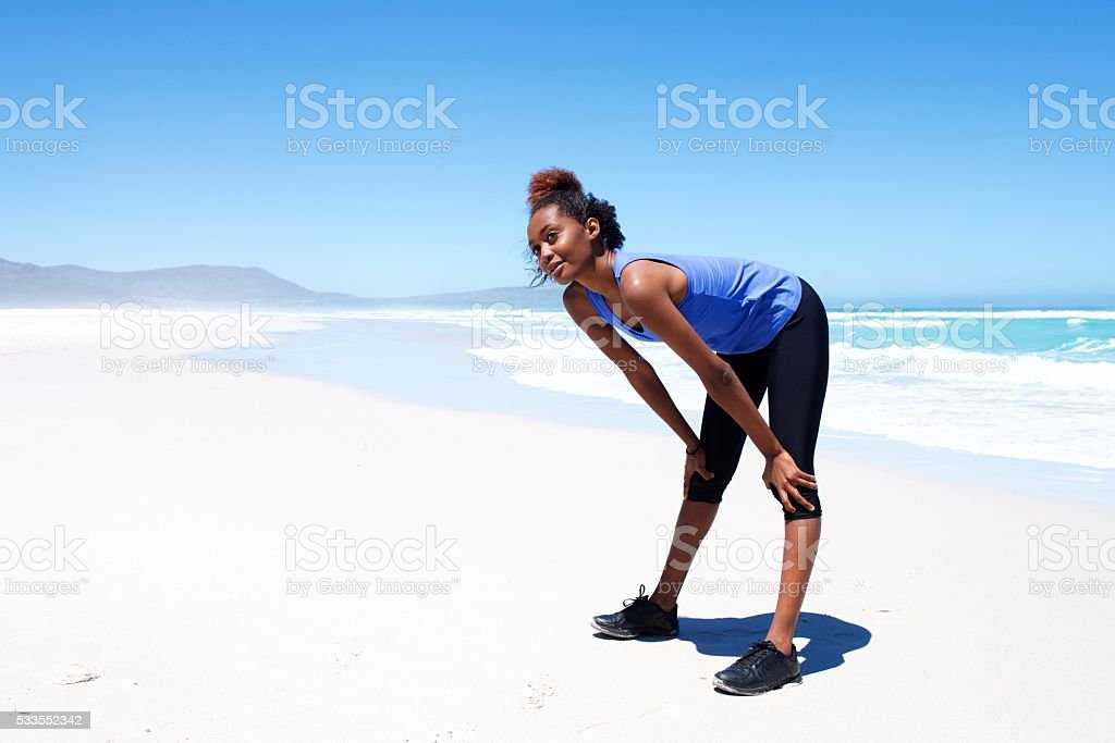 Woman taking a break during workout on the beach stock photo