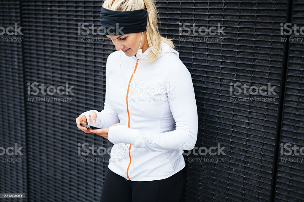 Woman taking a break form workout using mobile phone stock photo