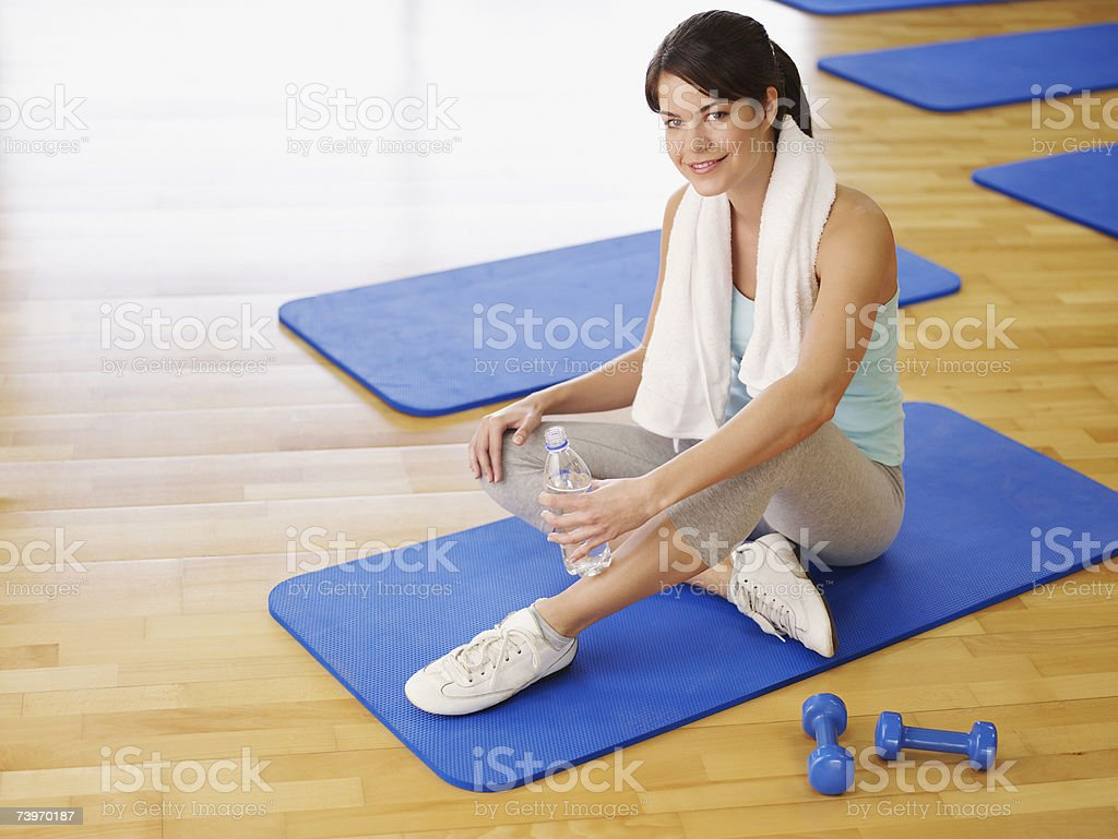 Woman taking a break from doing mat exercises in a fitness studio royalty-free stock photo