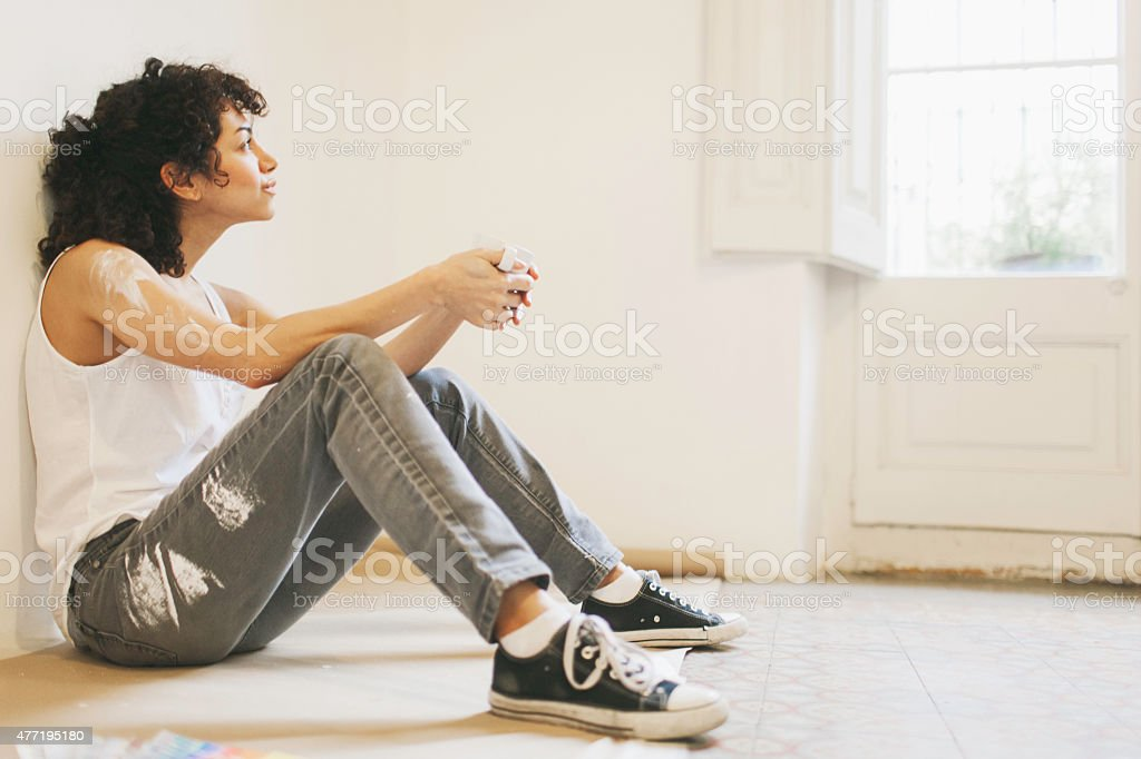 Woman taking a break while painting apartment. stock photo