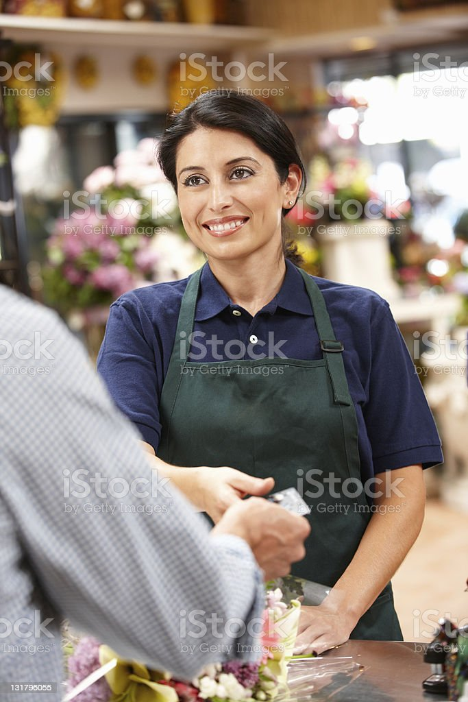 Woman taking a customers card while working at a florist stock photo