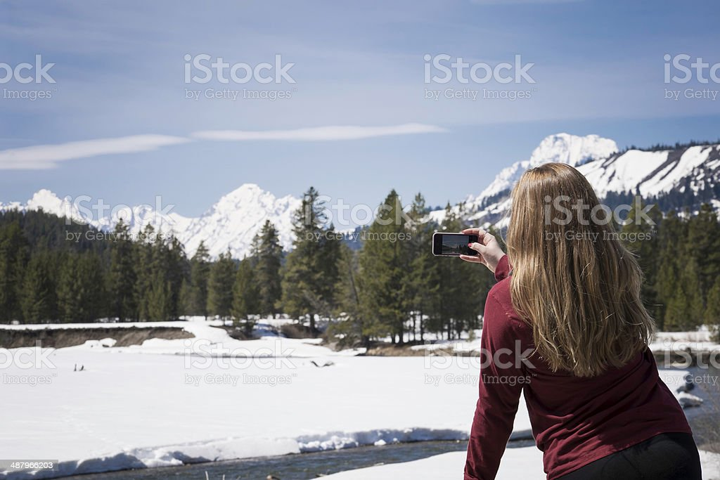 Woman Taking a Photo on Her Phone in the Tetons stock photo