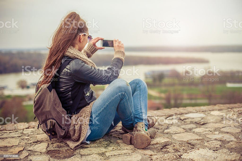 Woman taking a photo with cell phone stock photo