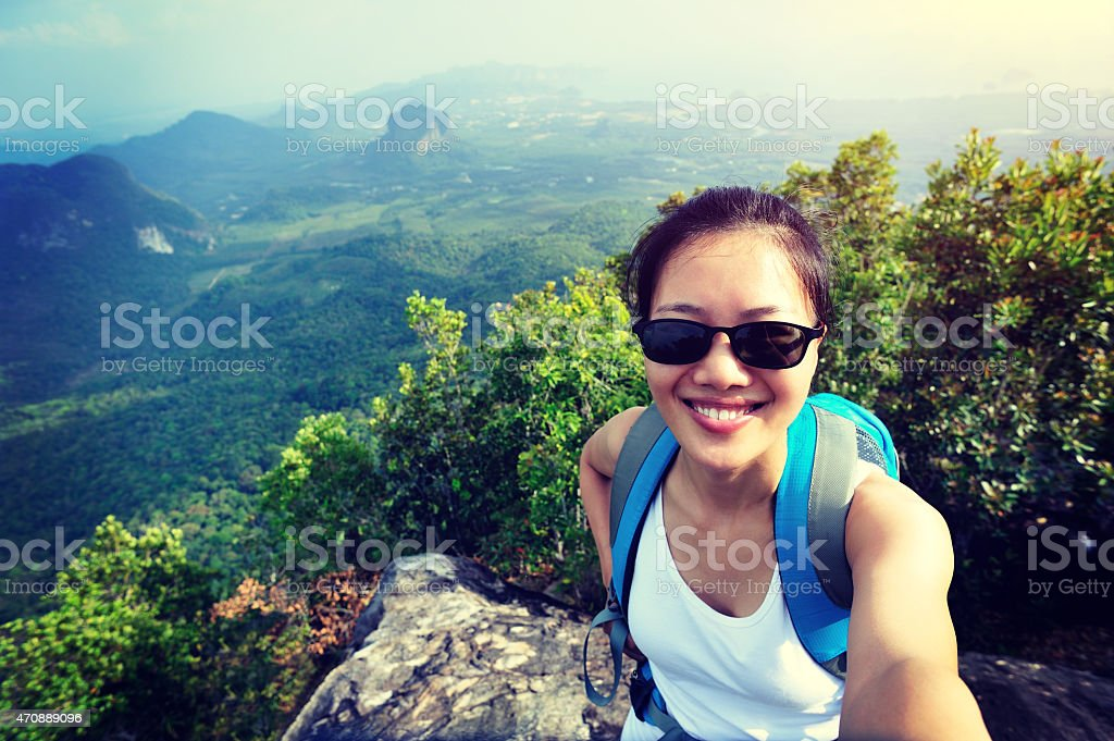 Woman taking a selfie in front of a mountain landscape stock photo