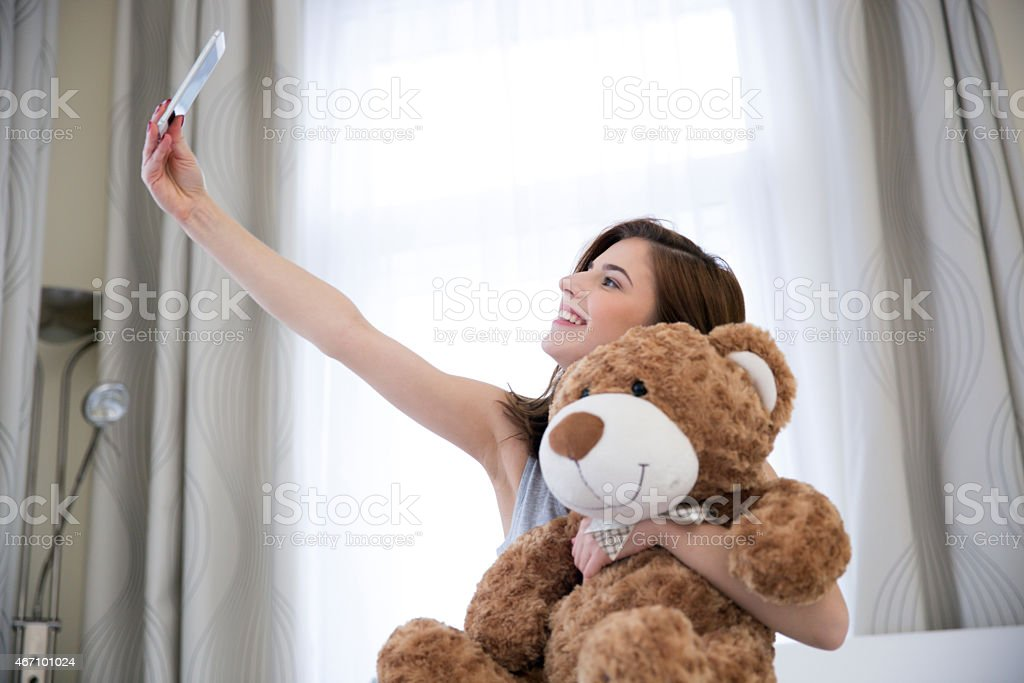 woman taking a selfie portrait with teddy bear stock photo