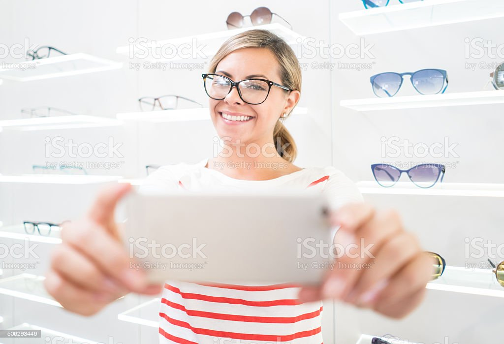 Woman taking a selfie with glasses at the optician stock photo