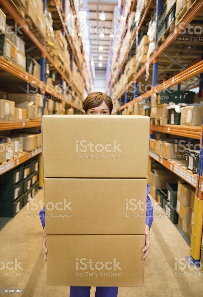 Woman taking a stack of boxes from narrow warehouse lane stock photo