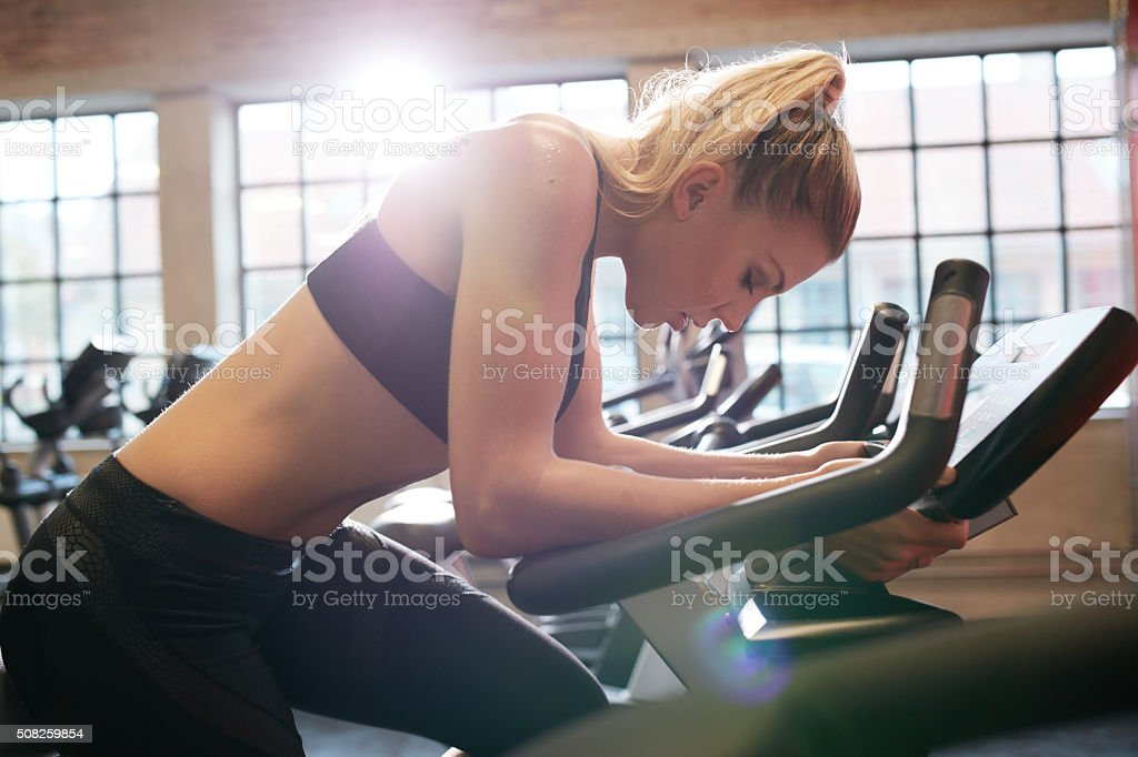 Woman taking break during cycling workout in gym stock photo