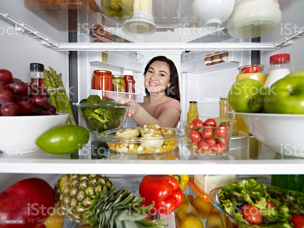 Woman Taking Broccoli From Fridge stock photo